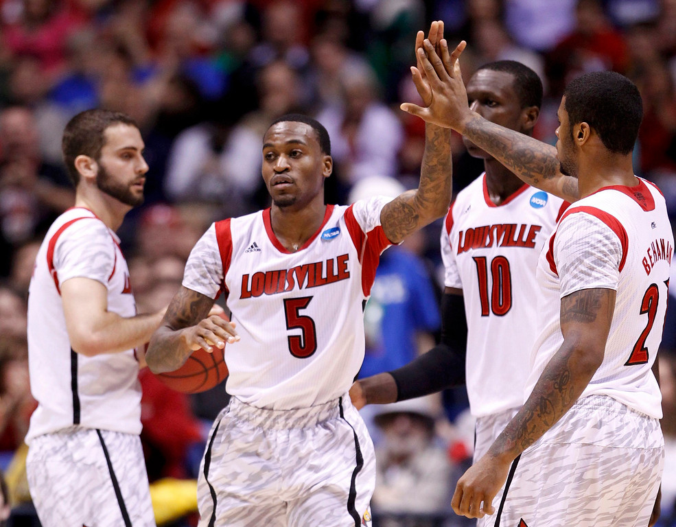 . Louisville Cardinals guard Kevin Ware (5) slaps hands with teammate Chane Behanan (R) after scoring against the Oregon Ducks during their Midwest Regional NCAA men\'s basketball game in Indianapolis, Indiana, March 29, 2013. REUTERS/Matt Sullivan