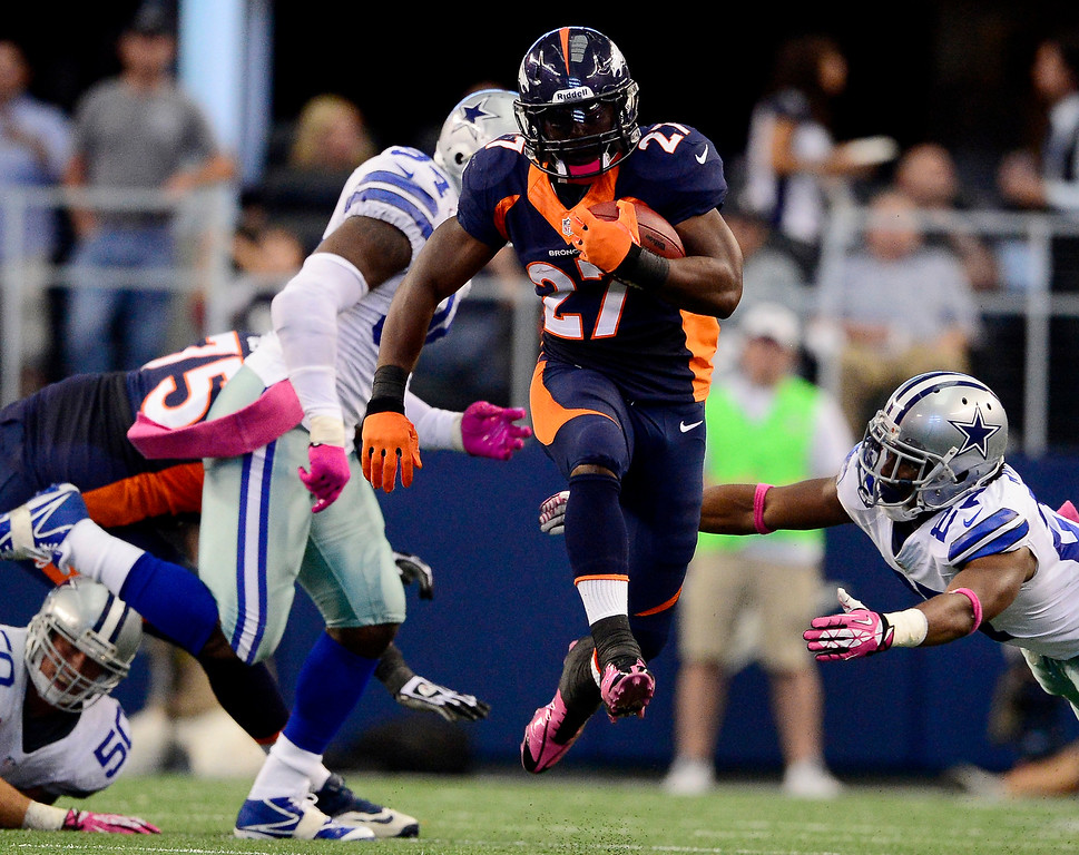 . Knowshon Moreno (27) of the Denver Broncos gets some air while running past J.J. Wilcox (27) of the Dallas Cowboys during the first half of action at AT&T Stadium in Dallas. (Photo by AAron Ontiveroz/The Denver Post)