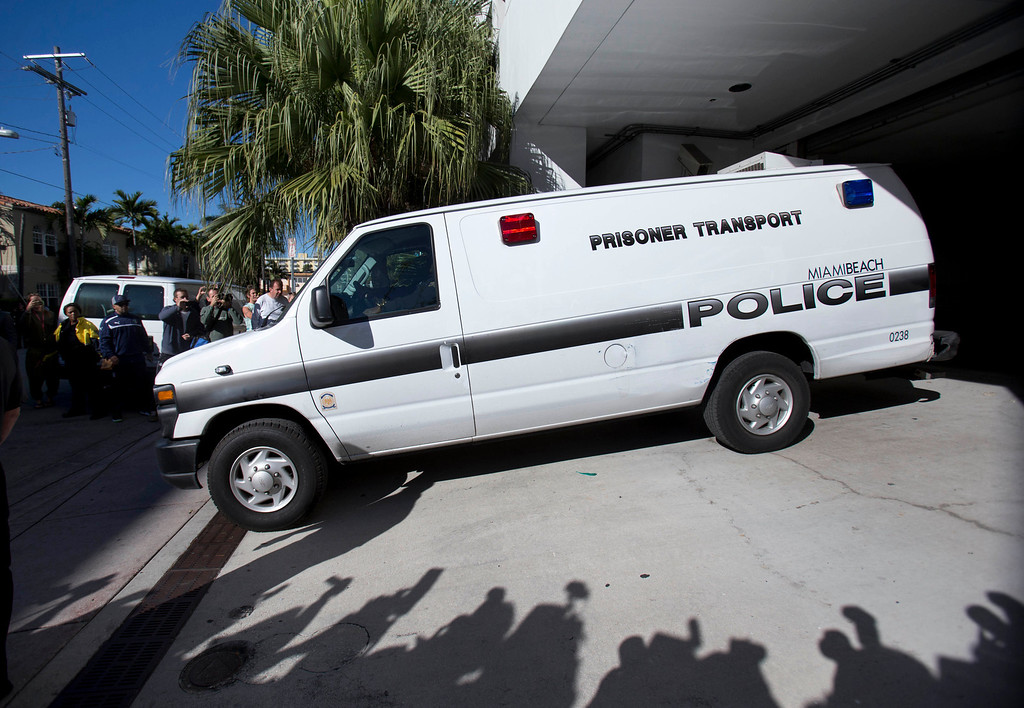. A Miami Beach, Fla., police prisoner transport van leaves the Miami Beach Police building believed to be transporting pop singer Justin Bieber and R&B singer known as Khalil after their arrest, Thursday, Jan. 23, 2014 in Miami Beach.   Bieber and Khalil both face drag-racing and driving under the influence charges. (AP Photo/Wilfredo Lee)