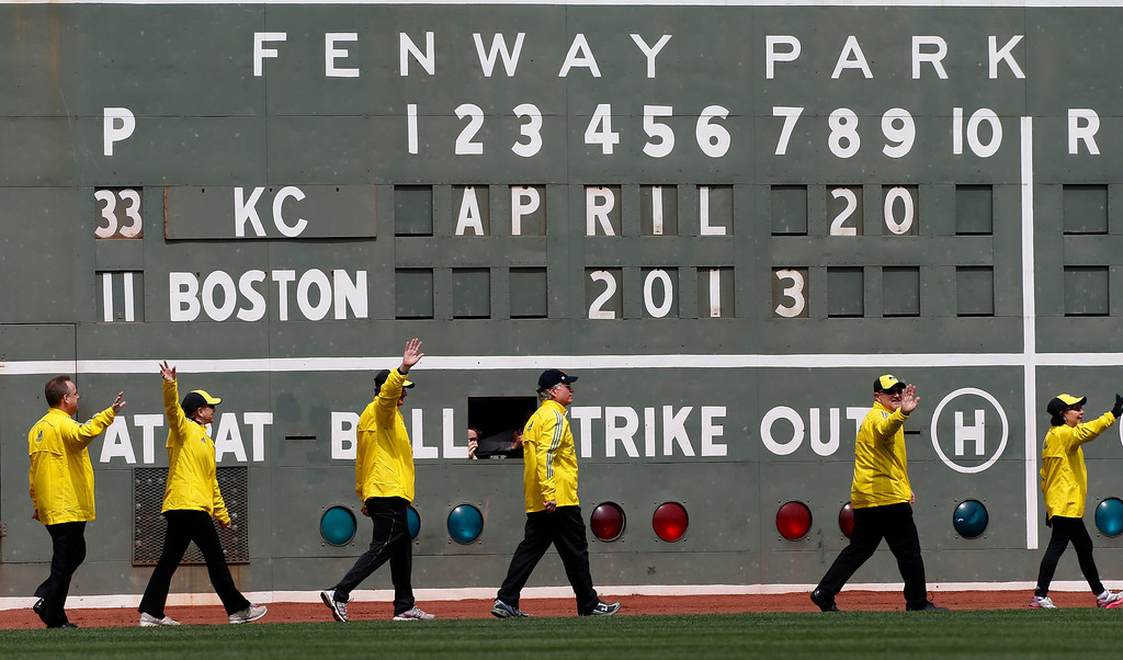 . Boston Marathon volunteer workers walk onto the field before a baseball game between the Boston Red Sox and the Kansas City Royals in Boston, Saturday, April 20, 2013. (AP Photo/Michael Dwyer)