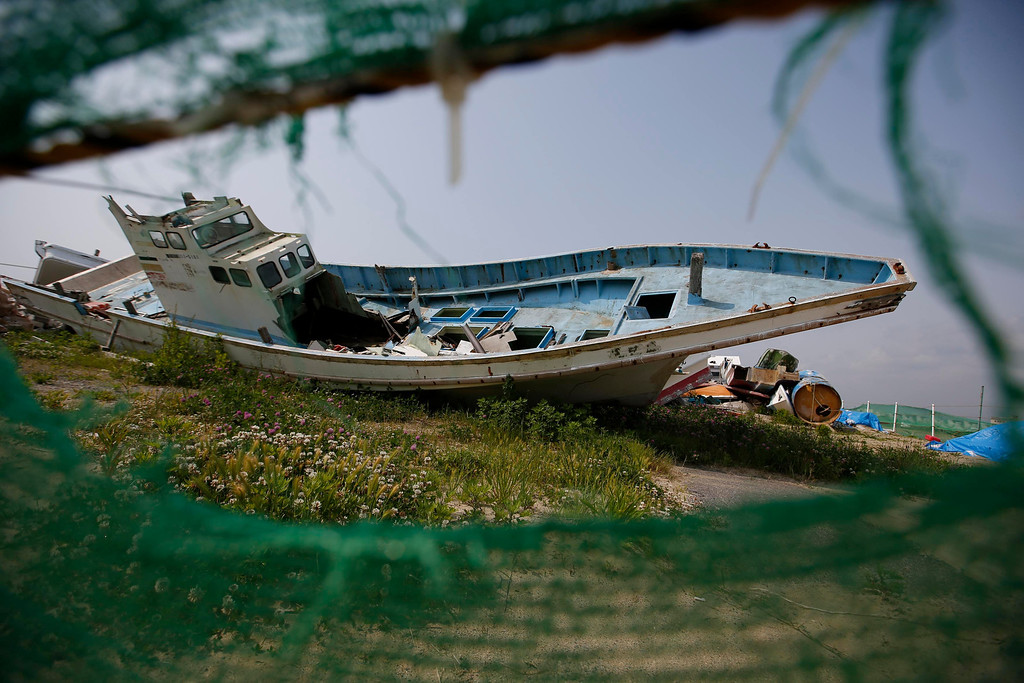 . A boat destroyed by the March 11, 2011 tsunami and earthquake lies in Yotsukura port in Iwaki, about 40 km (25 miles) south of the tsunami-crippled Fukushima Daiichi nuclear power plant, Fukushima prefecture May 27, 2013. Commercial fishing has been banned near the tsunami-crippled nuclear complex since the March 2011 tsunami and earthquake. The only fishing that still takes place is for contamination research, and is carried out by small-scale fishermen contracted by the government. Picture taken May 27, 2013. REUTERS/Issei Kato
