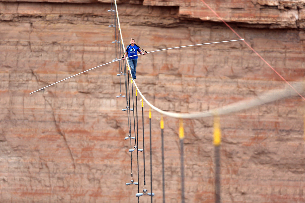 . Aerialist Nik Wallenda walks a 2-inch-thick steel cable taking him a quarter mile over the Little Colorado River Gorge, Ariz. on Sunday, June 23, 2013. The daredevil successfully traversed the tightrope strung 1,500 feet above the chasm near the Grand Canyon in just more than 22 minutes, pausing and crouching twice as winds whipped around him and the cable swayed. (AP Photos/Discovery Channel, Tiffany Brown)