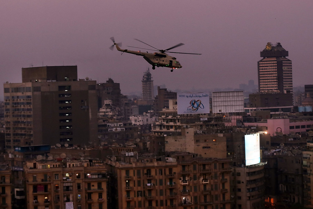 . An Egyptian military helicopter flies over Tahrir Square after a broadcast by the head of the Egyptian military confirming that they will temporarily be taking over from the country\'s first democratically elected president Mohammed Morsi on July 3, 2013 in Cairo, Egypt. As unrest spreads throughout the country, at least 23 people were killed in Cairo on Tuesday and over 200 others were injured. It has been reported that the military has taken over the state television.  (Photo by Spencer Platt/Getty Images)