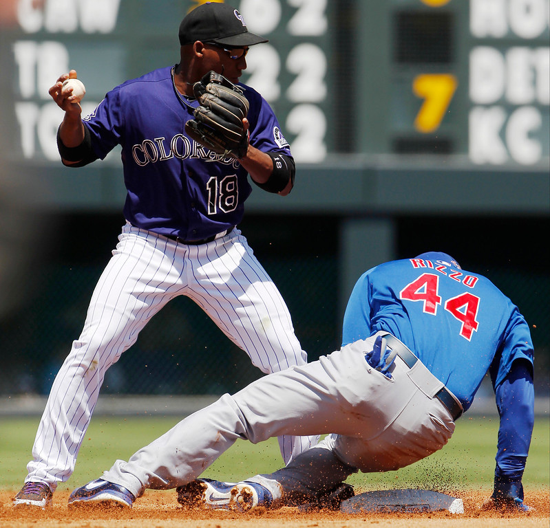 . Colorado Rockies second baseman Johnny Herrera, left, forces out Chicago Cubs\' Anthony Rizzo (44) at second base on a ground ball hit by Alfonso Soriano in the first inning of a baseball game in Denver, Sunday, July 21, 2013. (AP Photo/David Zalubowski)