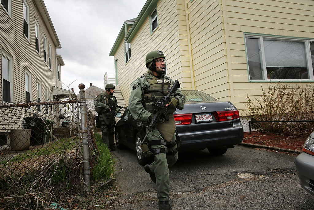 . Members of a police SWAT team conduct a door-to-door search for 19-year-old Boston Marathon bombing suspect Dzhokhar A. Tsarnaev on April 19, 2013 in Watertown, Massachusetts.  (Photo by Spencer Platt/Getty Images)