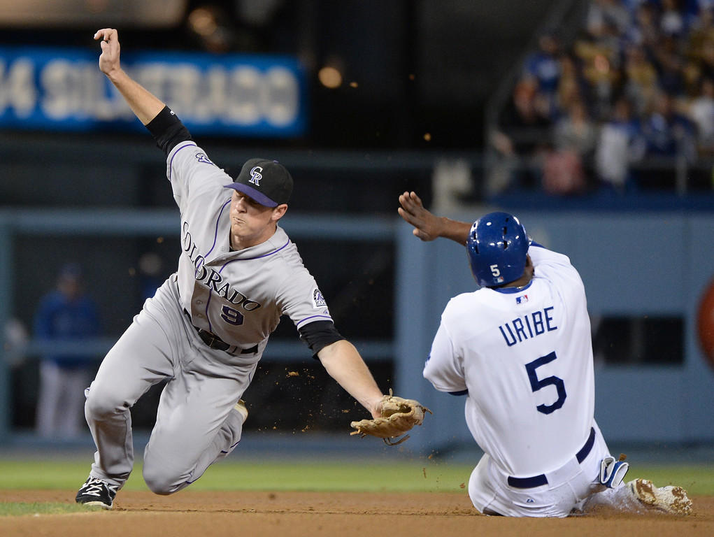. LOS ANGELES, CA - SEPTEMBER 27:  DJ LeMahieu #9 of the Colorado Rockies stretches for a throw to second base as Juan Uribe #5 of the Los Angeles Dodgers slides in safely during the third inning at Dodger Stadium on September 27, 2013 in Los Angeles, California.  (Photo by Harry How/Getty Images)