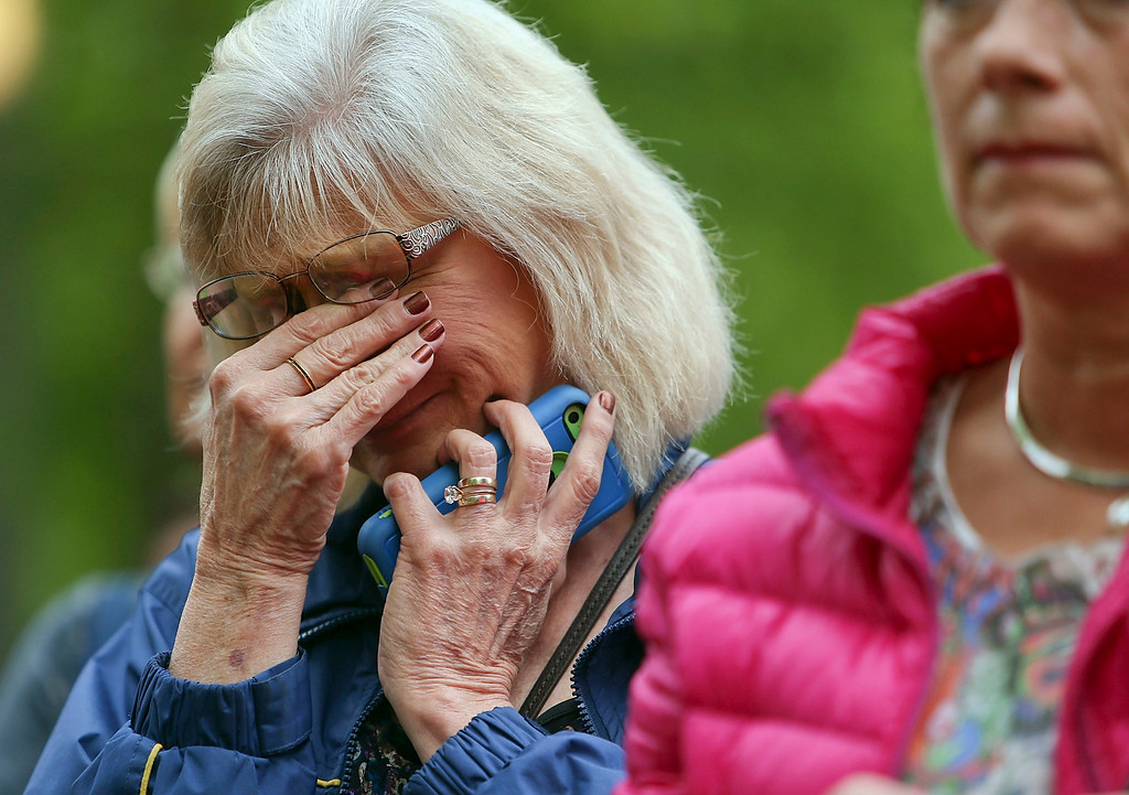 . A woman wipes away tears at the Ground Zero memorial site while watching the dedication ceremony of the National September 11 Memorial Museum at in New York on Thursday, May 15, 2014.  (AP Photo/Spencer Platt, Pool)