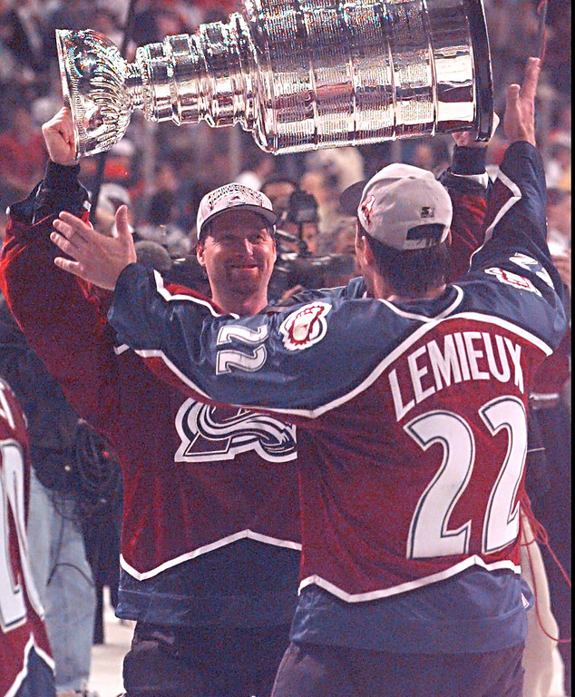 . Colorado Avalanche goalie Patrick Roy hands the Stanley Cup to teammate Claude Lemieux after the Avalanche defeated the Florida Panthers 1-0 in triple overtime to sweep the finals in four games Monday, June 10, 1996, in Miami. (AP Photo/Marta Lavandier)