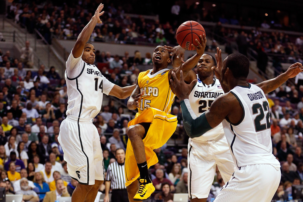 . Erik Buggs #15 of the Valparaiso Crusaders drives for a shot attempt against Gary Harris #14, Derrick Nix #25 and Branden Dawson #22 of the Michigan State Spartans during the second round of the 2013 NCAA Men\'s Basketball Tournament at at The Palace of Auburn Hills on March 21, 2013 in Auburn Hills, Michigan.  (Photo by Gregory Shamus/Getty Images)