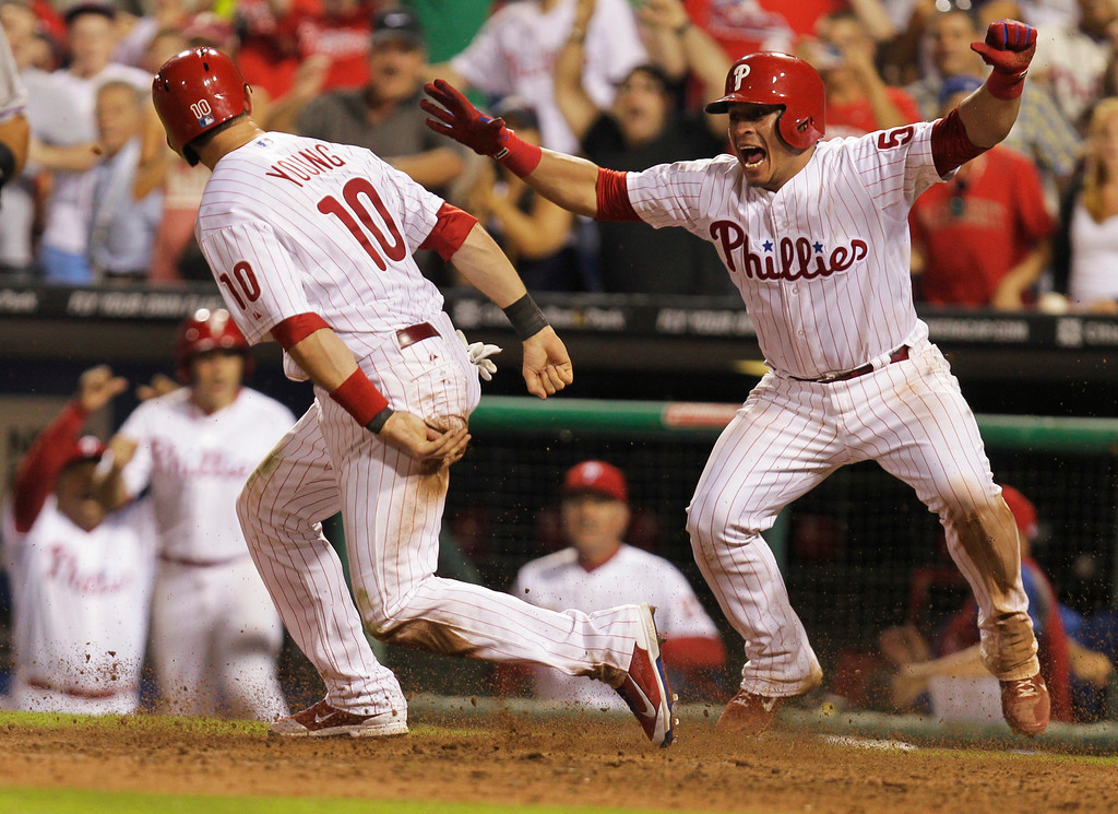 . Philadelphia Phillies\' Michael Young, left, is cheered by teammate Carlos Ruiz after making the game-winning run on a hit by Domonic Brown during the ninth inning of a baseball game to defeat the Colorado Rockies 5-4, Thursday, Aug. 22, 2013, in Philadelphia. (AP Photo/Laurence Kesterson)