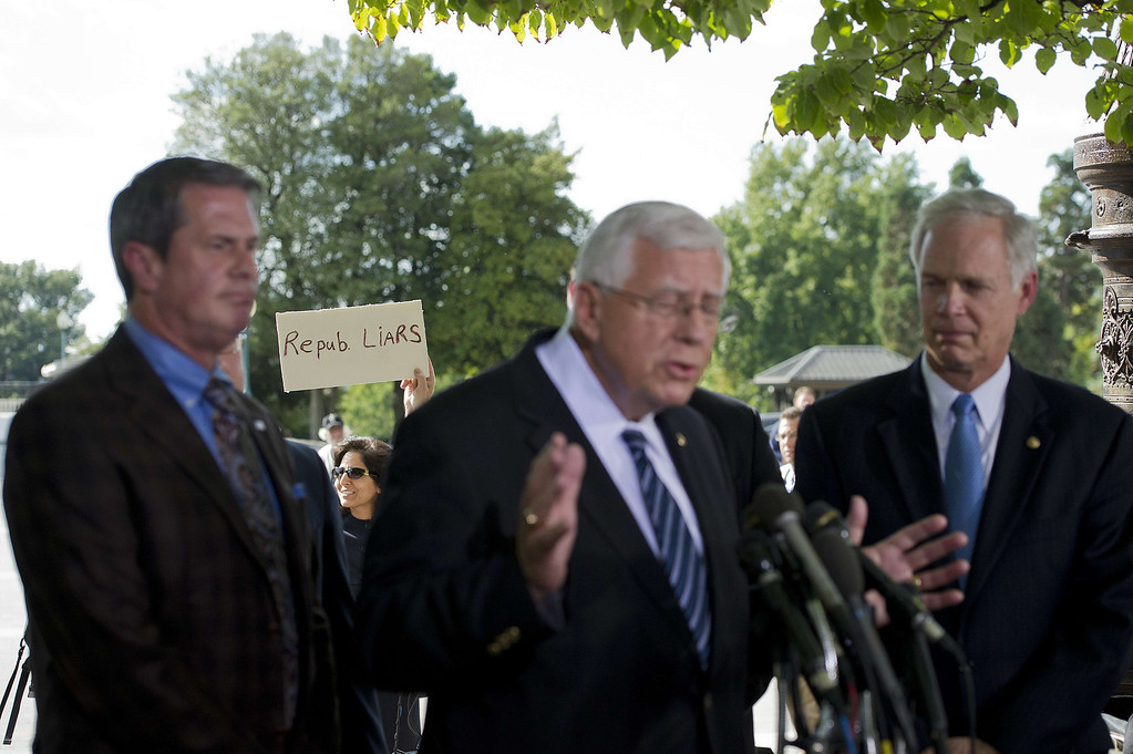 . A protester holds up a placard calling republicans liars as US Senator David Vitter, R-Lousiana (L), US Senator Micheal Enzi (C), R-Wyoming, and US Senator Ron Johnson (R), R-Wisconsin, speak during a press conference on Capitol Hill in Washington, DC, September 30, 2013. Senator Vitter penned an amendment to nix subsidies for the health care of congressional staffers.                          AFP PHOTO/Jim WATSONJIM WATSON/AFP/Getty Images