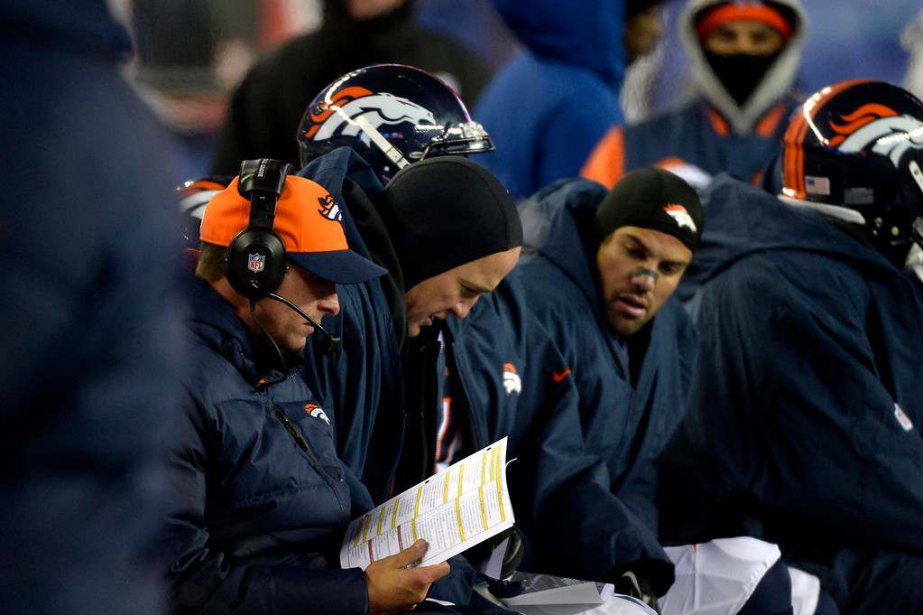 . Quarterback Peyton Manning #18 of the Denver Broncos looking over pages and pages on the bench in overtime. The patriots win 43-31 at Gillette Stadium in Foxborough MA, November 24, 2013 Denver. (Photo By Joe Amon/The Denver Post)