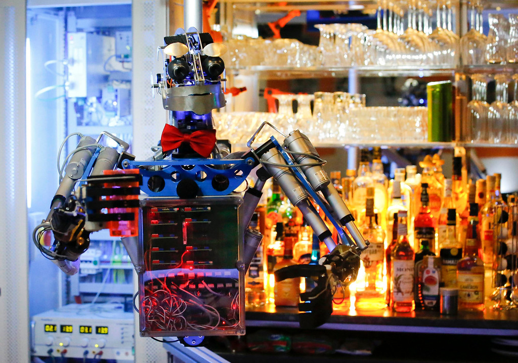""". Humanoid robot bartender \""""Carl\"""" is on standby to prepare a drink for guests at the Robots Bar and Lounge in the eastern German town of Ilmenau, July 26, 2013. \""""Carl\"""", developed and built by mechatronics engineer Ben Schaefer who runs a company for humanoid robots, prepares spirits for the mixing of cocktails and is able to interact with customers in small conversations. Picture taken July 26, 2013. REUTERS/Fabrizio Bensch"""