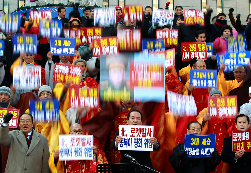 """. South Korean religious leaders raise placards and shout slogans during a rally denouncing North Korea\'s rocket launch in Seoul, South Korea, Wednesday, Dec. 12, 2012. North Korea fired a long-range rocket Wednesday in its second launch under its new leader, South Korean officials said, defying warnings from the U.N. and Washington only days before South Korean presidential elections. The words read \""""Denounce North Korea\'s rocket launch and overthrow family succession through three generations!\"""" (AP Photo/Ahn Young-joon)"""
