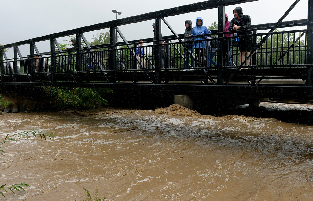 . BOULDER, CO. - SEPTEMBER12:  Pedestrians watch the rising Boulder Creek from a  bridge on 28th Street in Boulder CO September 12, 2013. Record-breaking rain turned normally quiet creeks into raging, brown torrents that swept through Boulder on Thursday, flooding homes, swamping cars and closing roads and schools. (Photo By Craig F. Walker / The Denver Post)