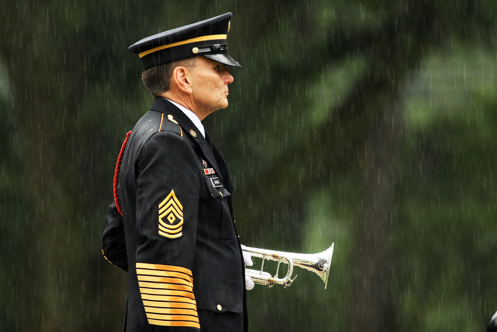 . A bugler stands at attention in the rain at the funeral of Sgt. 1st Class Edward Kramer at Wilmington National Cemetery on July 9, 2009 in Wilmington, North Carolina. Kramer and three others died when an IED went off near the Humvee they were in, according to a statement from the Defense Department. It was the last day of regular combat operations for U.S. forces in Iraqi cities. The four deaths marked the North Carolina National Guard\'s largest single combat loss since World War II.  (Photo by Logan Mock-Bunting/Getty Images)