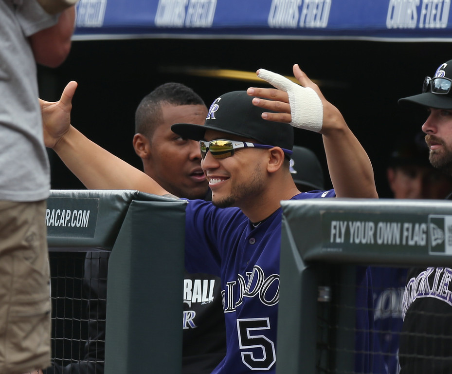 . His injured finger wrapped in a bandage, Colorado Rockies outfielder Carlos Gonzalez gestures to a member of the Los Angeles Dodgers as he looks on from the dugout in the first inning of a baseball game in Denver on Saturday, June 7, 2014. Gonzalez has been placed on the 15-day disabled list because of the finger. (AP Photo/David Zalubowski)
