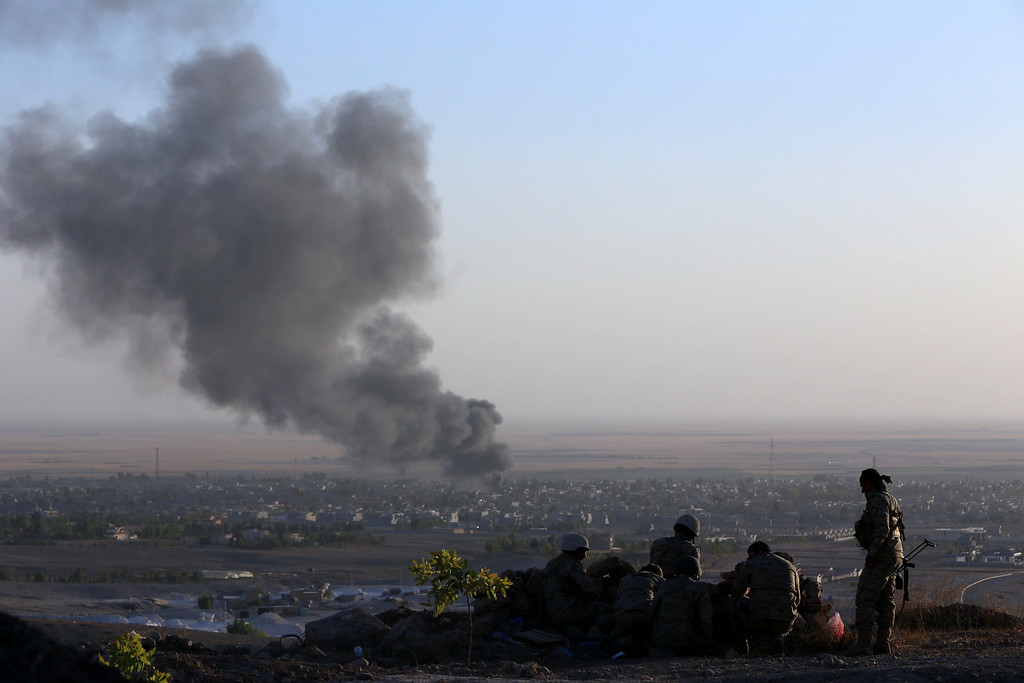 . Iraqi Kurdish Peshmerga fighters look on as smoke billows from the town Makhmur, about 280 kilometers (175 miles) north of the capital Baghdad, during clashes with Islamic State (IS) militants on August 9, 2014. Makhmur, is one of the areas that had been attacked by jihadist fighters in recent days. AFP PHOTO/SAFIN HAMED/AFP/Getty Images