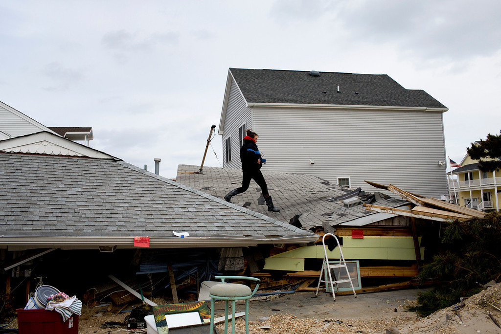 . Wendy Limandri, whose summer home was crushed between two houses, jumps from the roof of her collapsed home to her neighbor\'s in Ortley Beach, N.J., Nov. 25, 2012. Residents of the town were allowed to return on Sunday for the first time since Hurricane Sandy pulverized the area. (Todd Heisler/The New York Times)
