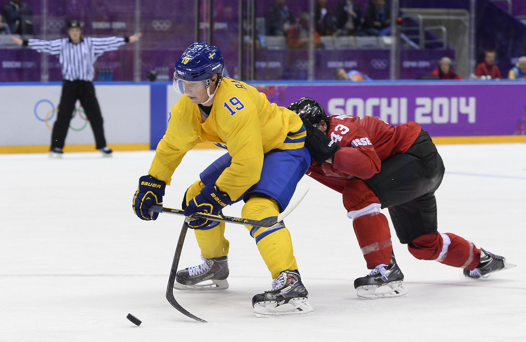 . Sweden\'s Nicklas Backstrom (L) vies with Switzerland\'s Morris Trachsler during the Men\'s Ice Hockey Group C match Sweden vs Switzerland at the Bolshoy Ice Dome at the Sochi Winter Olympics on February 14, 2014 in Sochi.   AFP PHOTO / JONATHAN NACKSTRAND/AFP/Getty Images