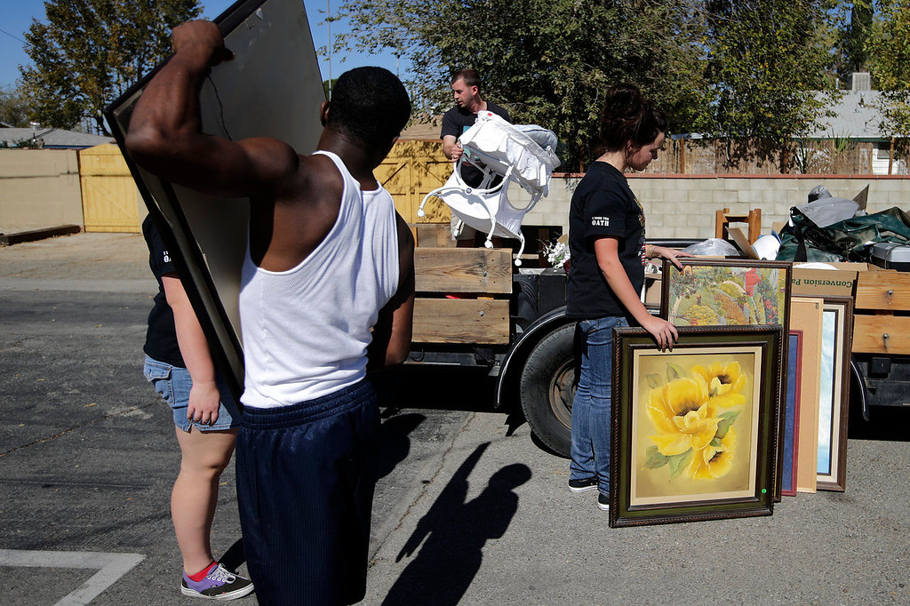 . Students and volunteers from Lancaster High School load items onto a trailer after a yard sale held to benefit Jerral Hancock, a 27-year-old Iraq war veteran who lost his left arm and is paralyzed from the waist down in a bomb explosion in Iraq, on Saturday, Oct. 26, 2013, in Lancaster, Calif. When the seniors in Jamie Goodreau\'s high school history class learned Hancock was once stuck in his modest mobile home for months when his handicapped-accessible van broke down, they decided to build him a new house from the ground up.  It would be their end-of-the-year project to honor veterans, something Goodreau\'s classes have chosen to do every year for the past 15 years. (AP Photo/Jae C. Hong)