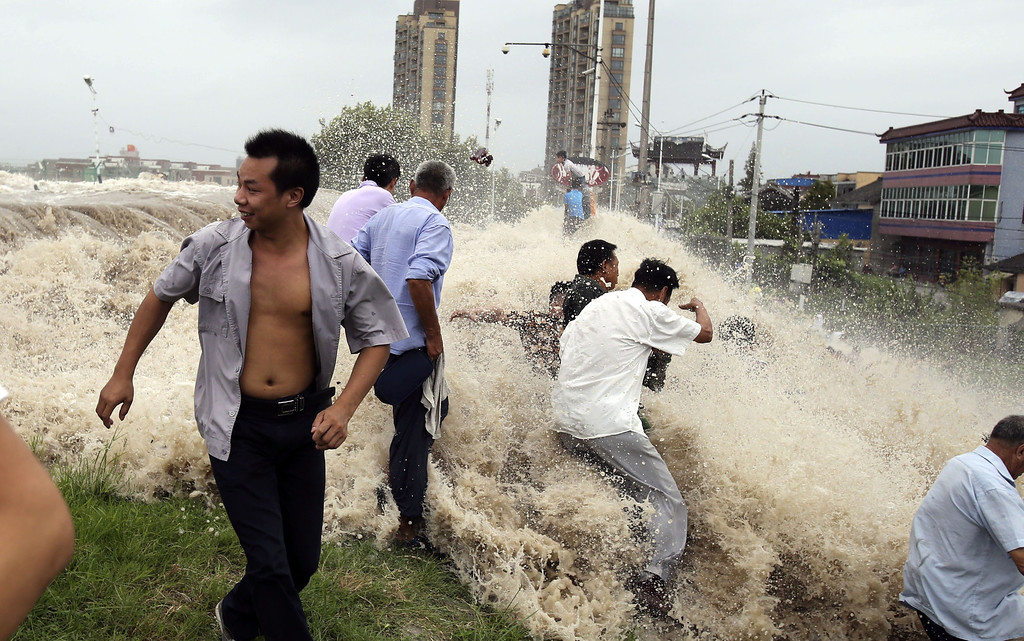 ". This picture taken on August 22, 2013 shows onlookers being washed away from huge waves from the ""Haining tide\"" - a daily occurrence when the river tides hit the banks of the city - as the waves surged higher than usual due to the influence of Typhoon Trami in the region in Haining, in eastern China\'s Zhejiang province. State media reported on August 23 that 30 people were injured and 11 still in hospital after the wave hit.  Typhoon Trami, the 12th typhoon to hit China this year, brought rainstorms and wreaked havoc in eastern China after landing in Fujian Province early on August 22.   AFP PHOTOSTR/AFP/Getty Images"