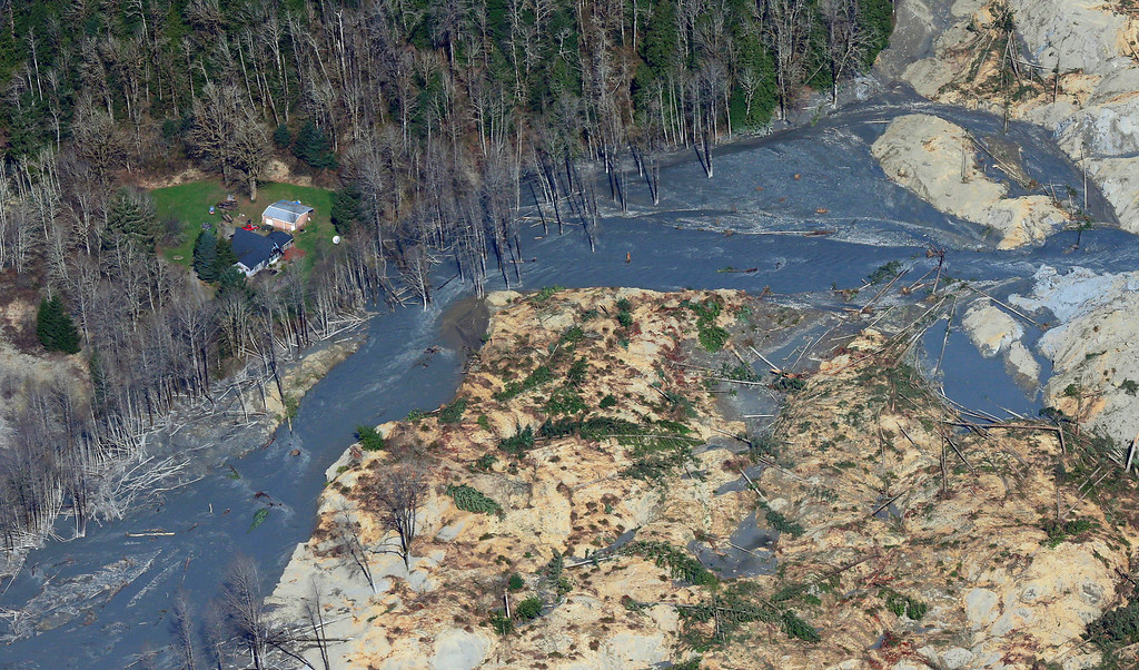 . An intact house sits at left at the edge of the massive mudslide that killed at least eight people and left dozens missing is shown in this aerial photo, Monday, March 24, 2014, near Arlington, Wash.  (AP Photo/Ted S. Warren)