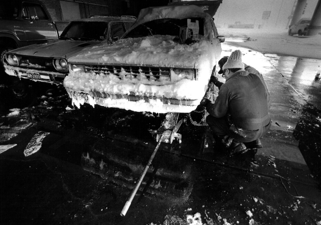 . Putting chains on a car at Denver Post loading doors during the blizzard of \'82. Lyn Alweis,  The Denver Post