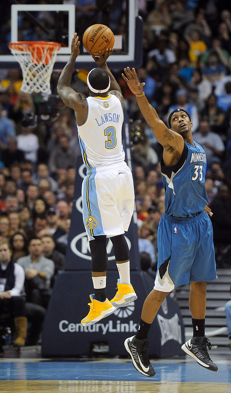 . Denver Nuggets guard Ty Lawson, left, shoots over Minnesota Timberwolves forward Dante Cunningham, right, in the second half of an NBA basketball game on Saturday, March 9, 2013, in Denver. The Nuggets won 111-88. (AP Photo/Chris Schneider)