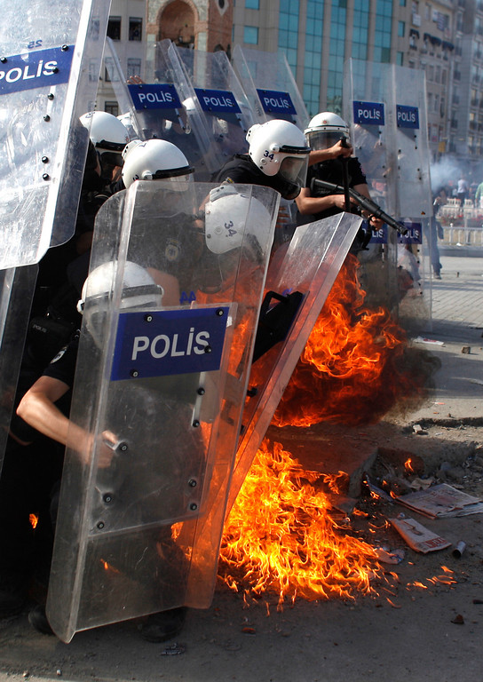 . A petrol bomb explodes in front of  riot policemen during clashes in Taksim Square in Istanbul, Turkey, Tuesday, June 11, 2013.  (AP Photo/Kostas Tsironis)