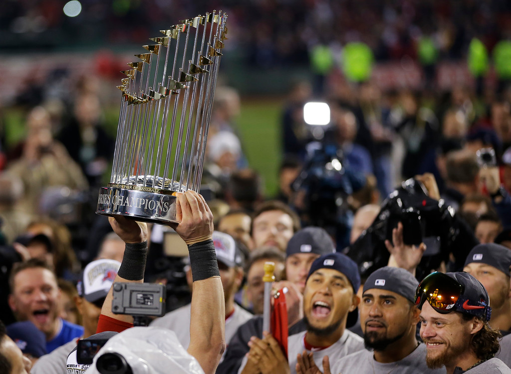 . A player holds up the championship trophy after defeating the St. Louis Cardinals in Game 6 of baseball\'s World Series Wednesday, Oct. 30, 2013, in Boston. The Red Sox won 6-1 to win the series. (AP Photo/Matt Slocum)