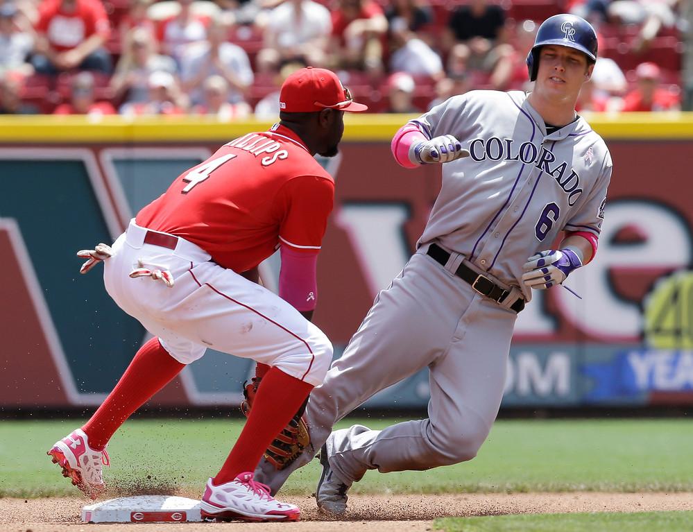 . Cincinnati Reds second baseman Brandon Phillips (4) tags out Colorado Rockies\' Corey Dickerson (6) trying to steal second base in the fourth inning of a baseball game, Sunday, May 11, 2014, in Cincinnati. (AP Photo/Al Behrman)