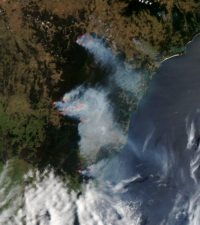 ". This October 21, 2013 NASA satellite image shows smoke(C-bluish) from wildfires burning near Sydney, Australia.  Firefighters were racing to tame an enormous blaze in southeastern Australia Monday with officials warning it could merge with others to create a ""mega-fire\"" if weather conditions worsen. Crews have been battling fires that flared in high winds and searing heat across the state of New South Wales last week with more than 200 homes so far destroyed and many others damaged. While dozens of blazes have been contained, 58 were still alight and 14 of them were out of control, enveloping Sydney in a thick white smoke haze that prompted warnings for people to stay indoors and avoid exercise. The main concern Monday was near the town of Lithgow west of Sydney where a huge fire that has already burned nearly 40,000 hectares (99,000 acres) was threatening the communities of Bilpin, Bell, Clarence and Dargan.   AFP PHOTO / NASA / HO/AFP/Getty Images"