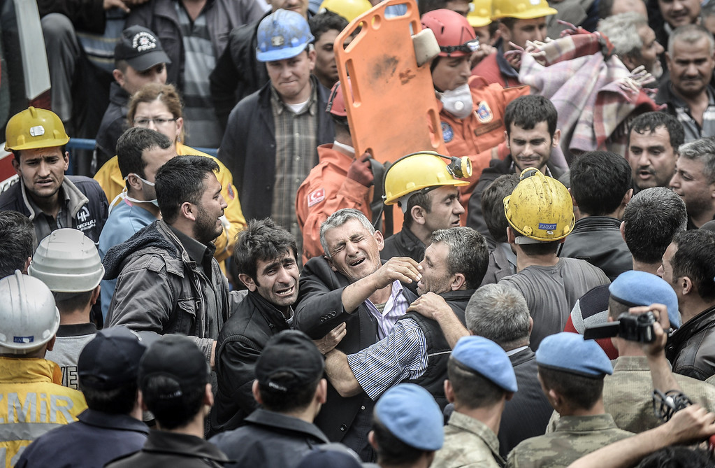 . Miners react as bodies of their dead co-workers are carried out of the mine after searching for hours hundreds of their colleagues who remain trapped underground on May 14, 2014 after an explosion and fire in their coal mine in the western Turkish province of Manisa killed at least 201 people.   AFP PHOTO/BULENT KILIC/AFP/Getty Images