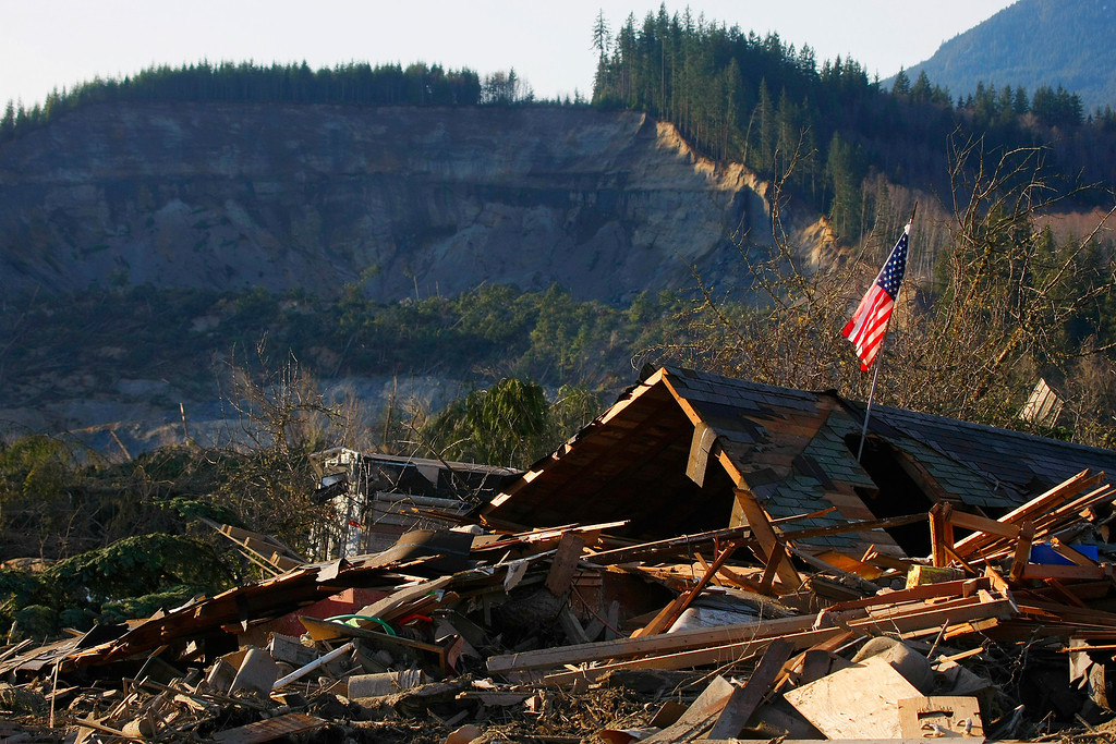 . A flag sits atop what was Cory Kuntz and family\'s home Sunday,  March 23, 2014. The family was at a baseball game Saturday morning when the fatal mudslide swept through the area, destroying everything on their property. The area where the land broke away is seen in the background. (AP Photo /The Herald, Genna Martin)