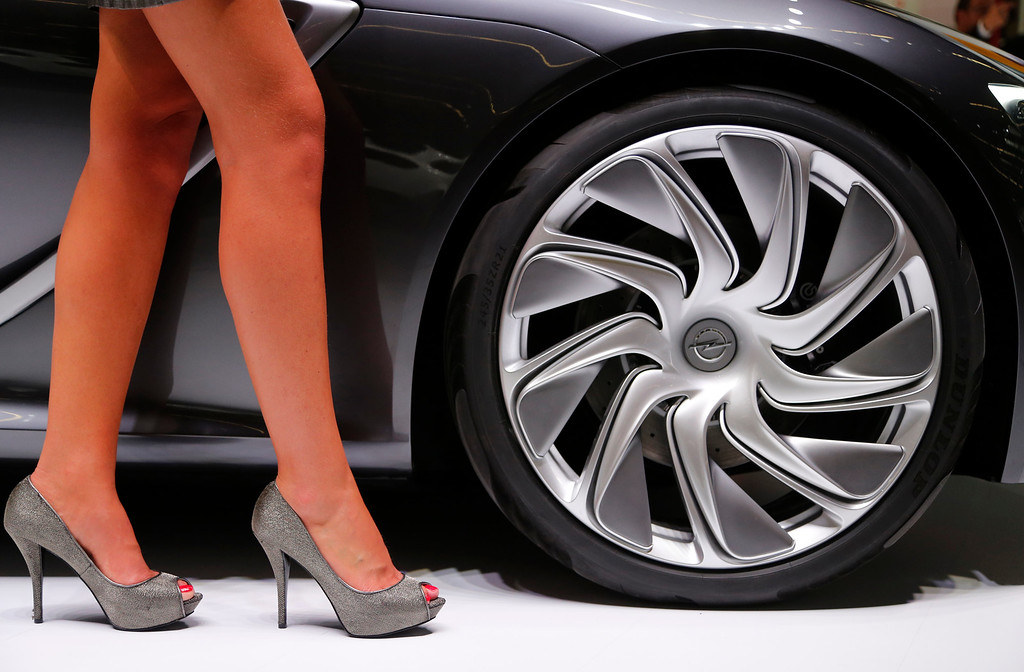. A hostess stands next to an Opel car during the first press day of the 65th Frankfurt Auto Show in Frankfurt, Germany, Tuesday, Sept. 10, 2013.  (AP Photo/Frank Augstein)