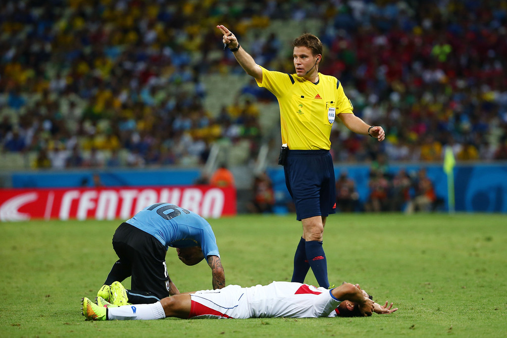 . Referee Felix Brych gestures as Michael Barrantes of Costa Rica lies on the pitch during the 2014 FIFA World Cup Brazil Group D match between Uruguay and Costa Rica at Castelao on June 14, 2014 in Fortaleza, Brazil.  (Photo by Robert Cianflone/Getty Images)