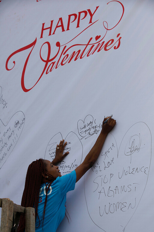 """. A student sign on a giant valentine card with inscriptions \'\' stop violence against women\'\' to support the \""""One Billion Rising\"""" global campaign in Lagos, Nigeria, Thursday, Feb. 14, 2013. Thousands of women and children in various cities in the country danced in the streets, in malls and other places to express support for the One Billion Rising movement, a worldwide call to end violence against women and girls. (AP Photo/Sunday Alamba)"""