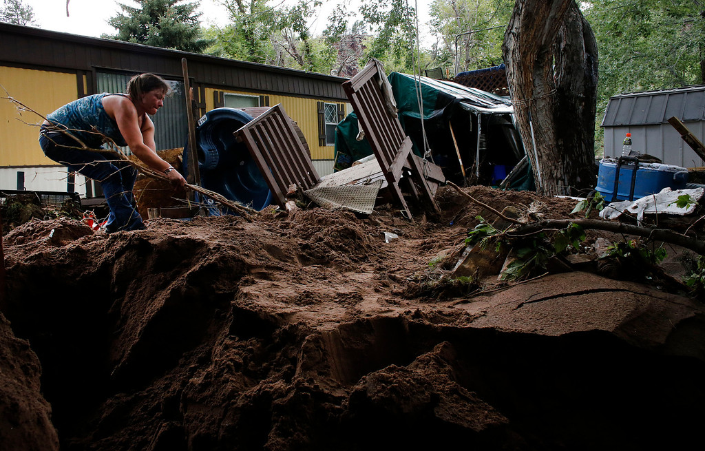 . Local resident Sanya Tuttle recovers parts of her home from debris after floods left homes and infrastructure in a shambles in Lyons, Colo., Friday Sept. 13, 2013. (AP Photo/Brennan Linsley)