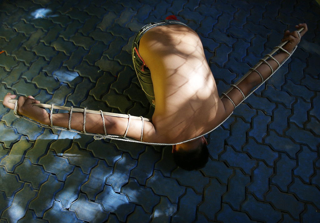 . A Filipino penitent rests as wooden stakes are tied to his arms during Maundy Thursday rituals to atone for sins, in suburban Mandaluyong, east of Manila, Philippines, on Thursday, March 28, 2013. The ritual is frowned upon by church leaders in this predominantly Roman Catholic country.(AP Photo/Aaron Favila)