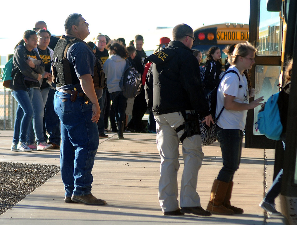 . Authorities stand guard as students are escorted from Berrendo Middle School after a shooting, Tuesday, Jan. 14, 2014, in Roswell, N.M. A shooter opened fire at the middle school, injuring at least two students before being taken into custody. Roswell police said the school was placed on lockdown. (AP Photo/Roswell Daily Record, Mark Wilson)