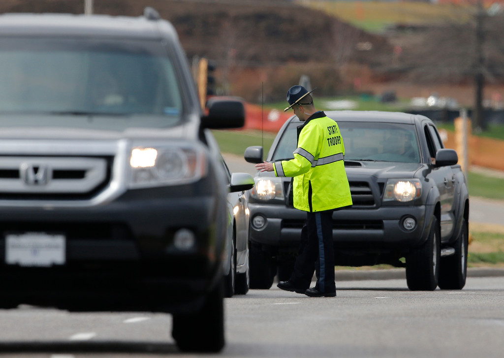 . A Kansas State Trooper controls traffic at the entrance of the Jewish Community Center after reports of a shooting in Overland Park, Kan., Sunday, April 13, 2014. (AP Photo/Orlin Wagner)