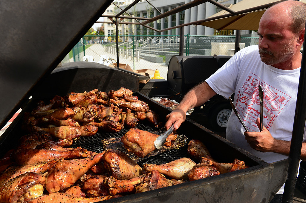 . Craig Johnson, of Sweet Lorraines Catering, slowly roasts gigantic turkey legs at the company\'s booth at  the Taste of Colorado at Civic Center Park in Denver on August 31, 2014.  The company will sell about 5,000 of the turkey legs over the course of the Labor day weekend.  The festival wraps up Monday September 1, 2014.  (Photo By Helen H. Richardson/ The Denver Post)