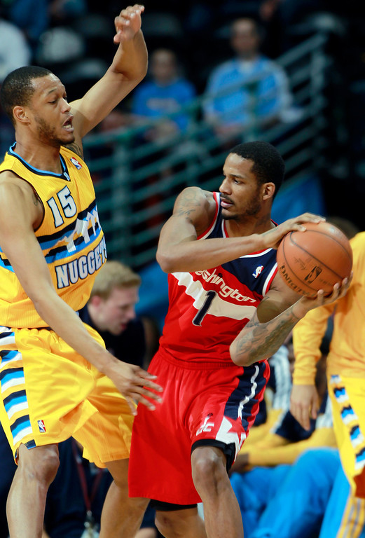 . Washington Wizards forward Trevor Ariza, right, looks to pass ball under pressure from Denver Nuggets forward Anthony Randolph in the third quarter of an NBA basketball game in Denver on Sunday, March 23, 2014. The Nuggets won 105-102. (AP Photo/David Zalubowski)