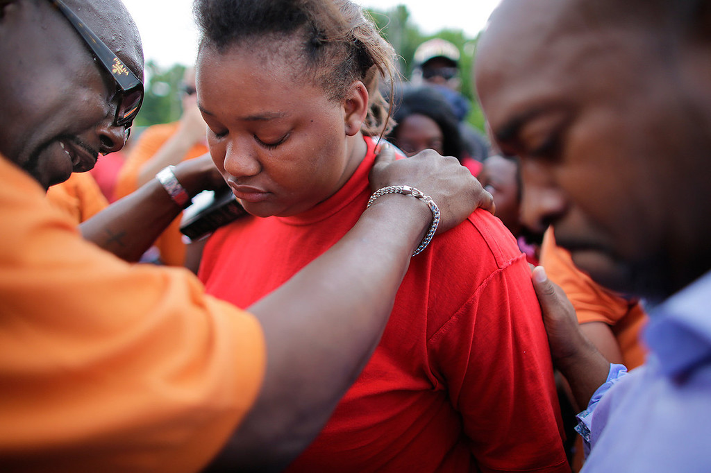 . Lisa North, 20, the mother of Ahlittia North, 6, is surrounded by friends and pastors, Rev. J. L. Hampton, left, and Toy Hodge, right, during a morning vigil near her daughter\'s body was found in a trash can, Wednesday, July 17, 2013 in Harvey, La. A suspect in the stabbing death of a 6-year-old girl whose body was found in a trash can only days after she disappeared from a suburban New Orleans apartment has confessed to the killing, a sheriff said Wednesday.  (AP Photo/The Times-Picayune, Chris Granger)