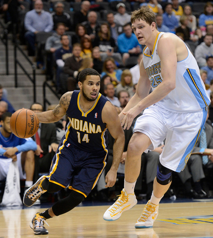. DENVER, CO. - JANUARY 28: Indiana Pacers point guard D.J. Augustin (14) drives on Denver Nuggets center Timofey Mozgov (25) during the second quarter January 28, 2013 at Pepsi Center. The Denver Nuggets host the Indiana Pacers in NBA action.  (Photo By John Leyba / The Denver Post)