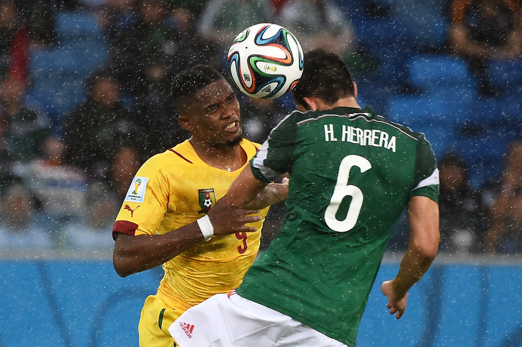 . Cameroon\'s forward and captain Samuel Eto\'o (L) fights for the ball with Mexico\'s midfielder Hector Herrera during a Group A football match between Mexico and Cameroon at the Dunas Arena in Natal during the 2014 FIFA World Cup on June 13, 2014. CHRISTOPHE SIMON/AFP/Getty Images