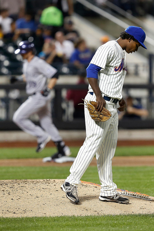 . New York Mets starting pitcher Jenrry Mejia stands on the mound as Colorado Rockies\' Charlie Blackmon rounds third base after hitting a solo home run in the sixth inning of a baseball game at Citi Field, Tuesday, Aug. 6, 2013, in New York. (AP Photo/John Minchillo)