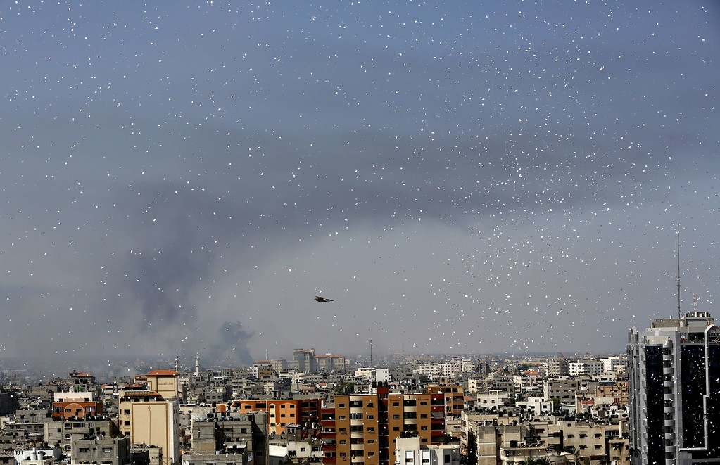 """. Flyers are dropped over Gaza City by the Israeli army urging residents to evacuate their homes on July 30, 2014. Israeli bombardments early on July 30 killed \""""dozens\"""" of Palestinians in Gaza, including at least 16 at a UN school, medics said, on day 23 of the Israel-Hamas conflict. AFP PHOTO / MOHAMMED  ABED/AFP/Getty Images"""