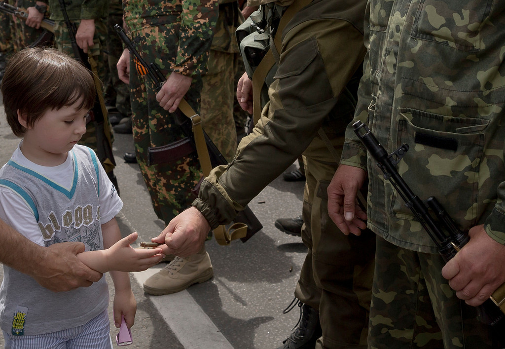 ". A man holds a child\'s hand to receive empty bullet cartridges offered by a pro-Russian gunman in Lenin square in Donetsk, Ukraine, Sunday, May 25, 2014. A convoy of an armored personnel carrier and seven trucks carrying several hundred heavily armed men drove through central Donetsk early Sunday afternoon and gunmen got out of the trucks, stood to attention and shot into the air in jubilation as a crowd of several thousand supporters cheered them and chanted: ""Heroes!\"". Ukraine\'s critical presidential election got underway Sunday under the wary scrutiny of a world eager for stability in a country rocked by a deadly uprising in the east. (AP Photo/Vadim Ghirda)"